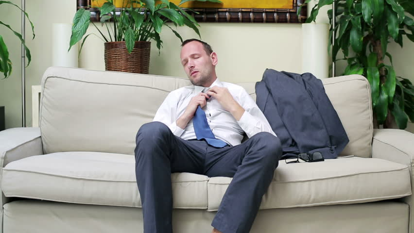 businessman coming back from work and sitting on the sofa