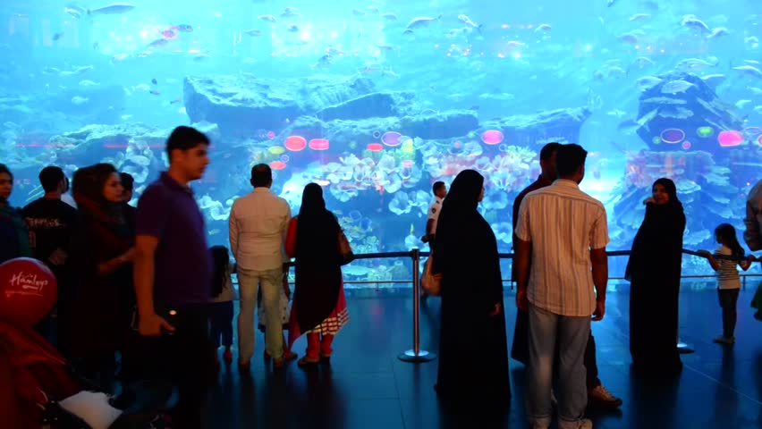 DUBAI, UAE - MARCH 27, 2014: People in front of the Oceanarium inside Dubai Mall. At over 12 million sq ft, it is the world's largest shopping mall.