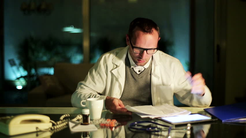 Doctor checking documents at night in office.
