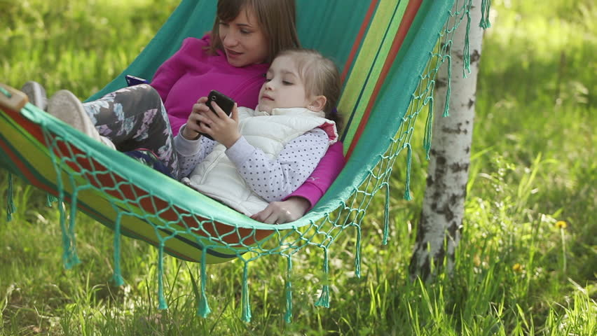Mother and daughter lying in a hammock outdoors. They held mobile phones | Shutterstock HD Video #6201257