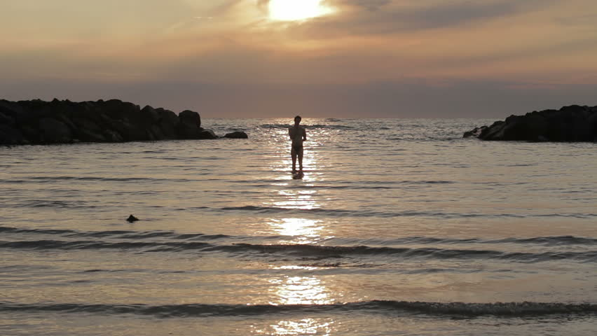 dressed woman in love runs to her man into the sea - hugs and kisses - sunset