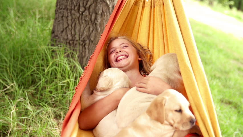 Laughing girl swinging in hammock with puppies in slow motion