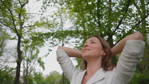 young, beautiful woman enjoying the fresh air in the forest. she threw her hands behind her head and breathes deeply, she looks very happy and relaxed. slow-motion