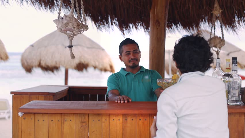 Hispanic woman chatting with barman at caribbean beach