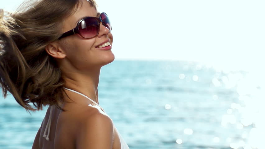 Beautiful young woman in bikini is styling her hair on the sea beach. Sunny summer by the sea. Slow motion. Filmed at 250 fps.