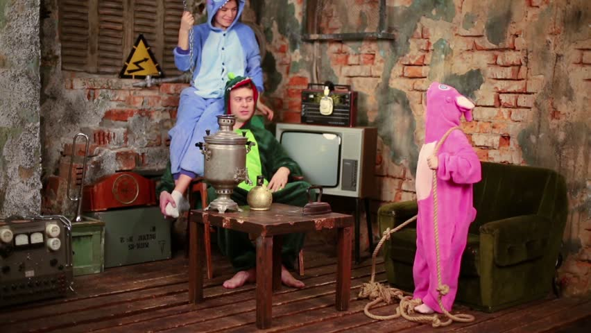 Family in colorful costumes of dragons at very old room with samovar and TV