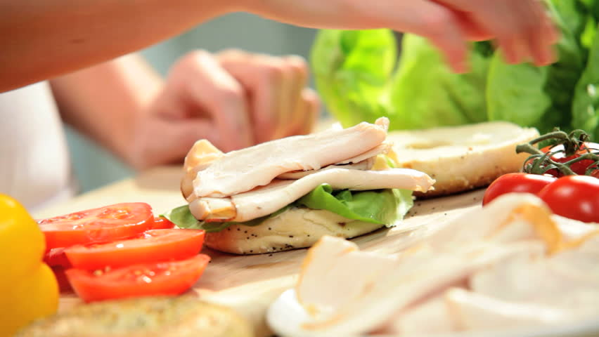 Female Hands Making Fresh Granary Bagel - Fresh granary bagel being filled with organic lettuce tomatoes sliced meat and cheese for delicious lunch sandwich close up hands