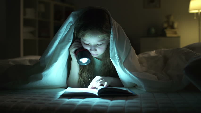 Dolly of girl resting in bed and reading aloud with the help of lantern