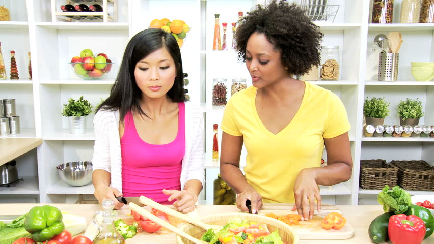 Multi Ethnic Females Preparing Healthy Living Meals - Young ethnic females preparing delicious organic salad vegetables home kitchen for healthy living meal