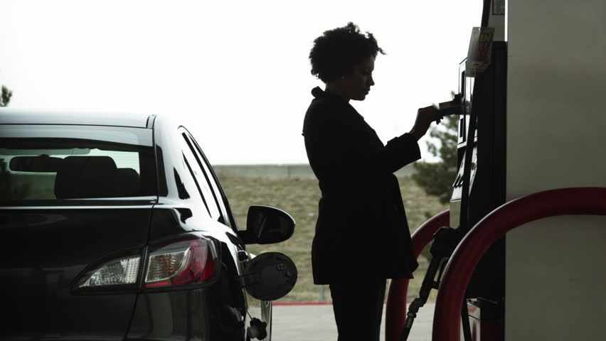 Medium Shot Woman refueling car at gas station