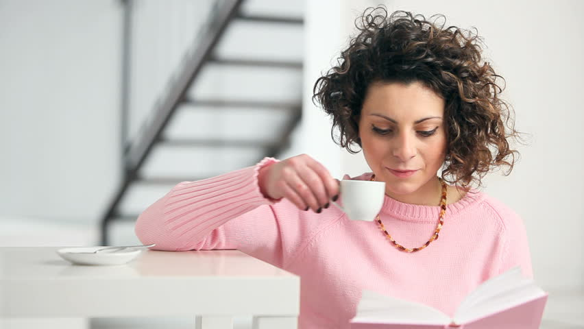 Young woman reading book at home and drinking coffee. HD 30 fps