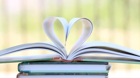 Book stack open page heart shape in wind, green garden background