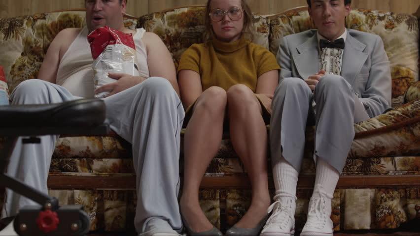 Medium Shot Overweight man wearing pajamas, holding bag of chips sitting by nerdy couple on sofa