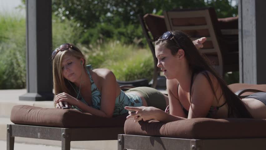 Medium Shot Two teenage (16-17) girls in bikini lying on sunloungers and listening music | Shutterstock HD Video #6373157