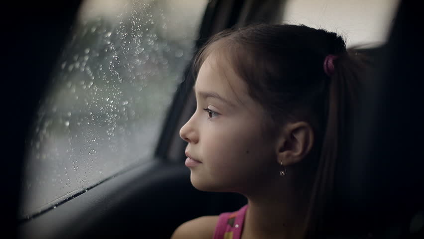 Little girl looking out from car window. Rainy weather