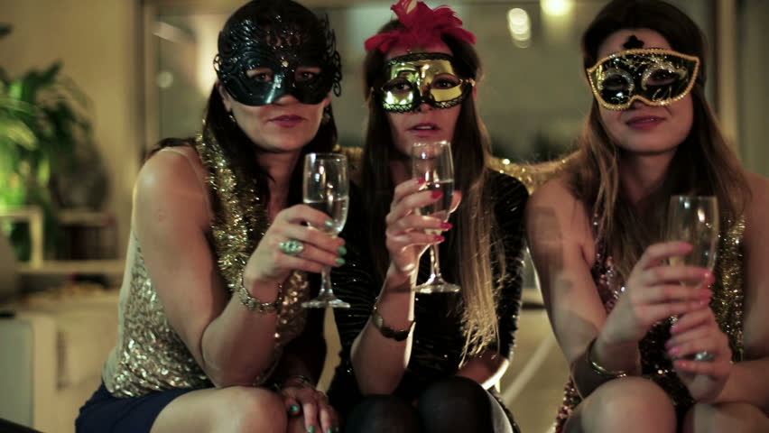 attractive women in masks making toast with glasses of champagne