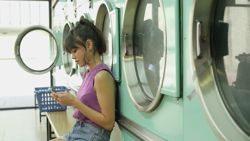 A Young Woman uses her smartphone whilst waiting for his Laundry