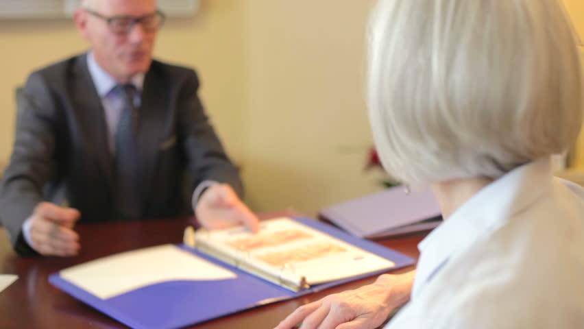 Senior Woman Talking To Financial Advisor In Office