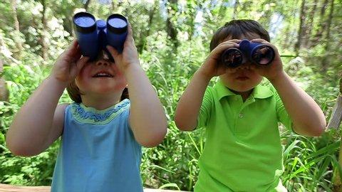 Kids Use Binoculars To Explore The Forest Around Them