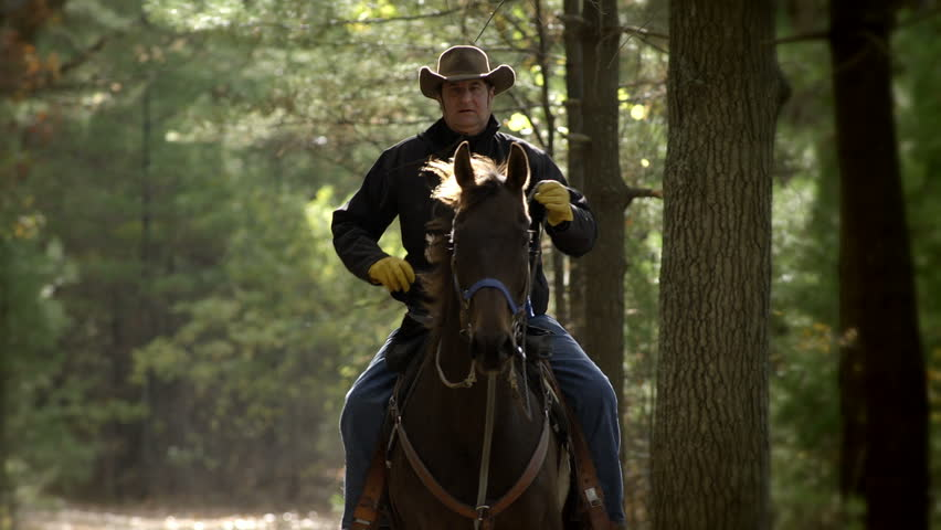 Medium shot of an older man riding a horse towards the camera in slow motion