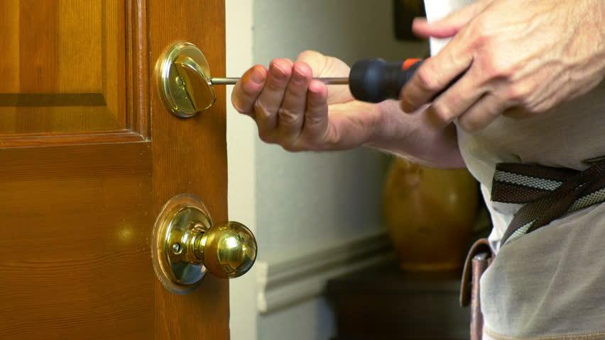 front door knob. A Handyman Removing Door Knob From Front Door. - 4K Stock Footage Clip