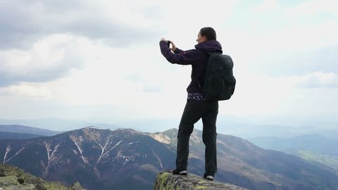 Young woman uses a smart phone to video a beautiful view in the mountains