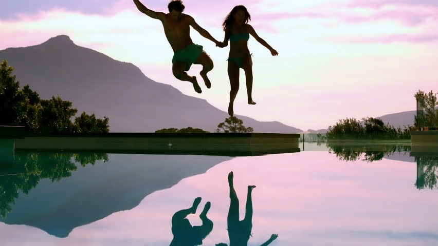 Couple jumping off cliff