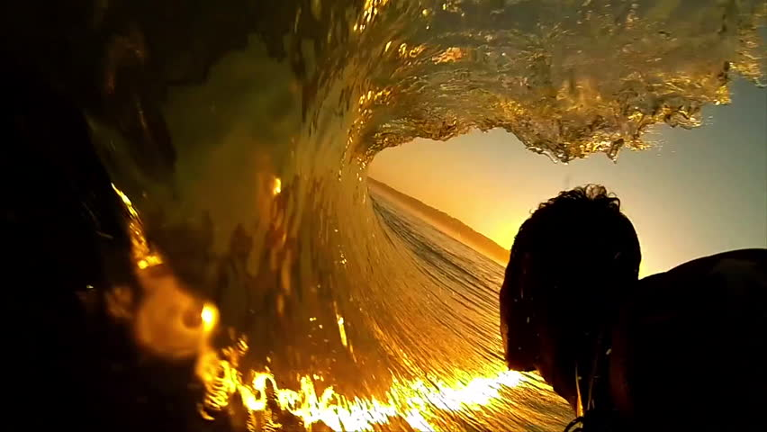 High contrast POV shot of silhouetted surfer as he rides through the barrel of a dark orange wave, with the sun setting ahead of him | Shutterstock HD Video #6596987
