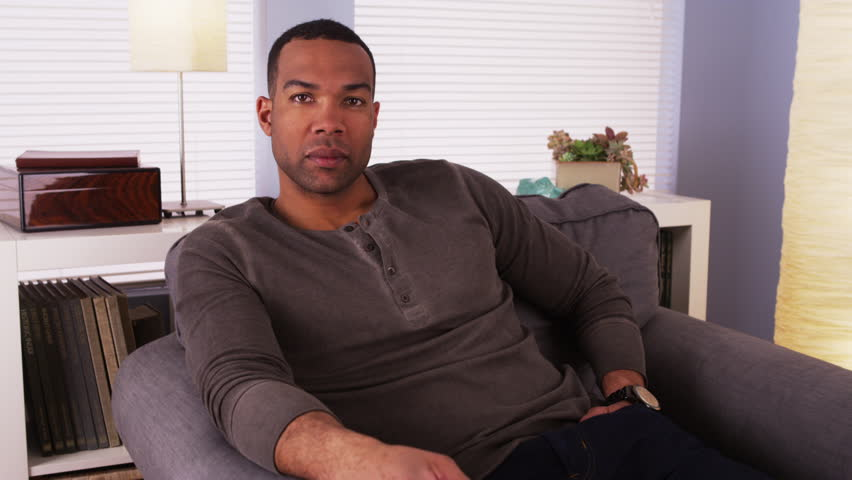 Black man resting on couch and looking at camera   Shutterstock HD Video #6617897