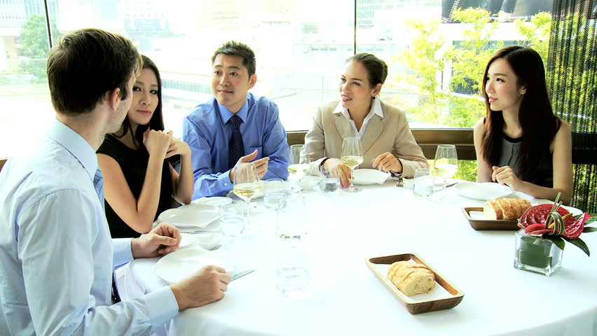 Successful male female Asian Chinese Caucasian corporate executives toasting each other business success dining restaurant | Shutterstock HD Video #6646505