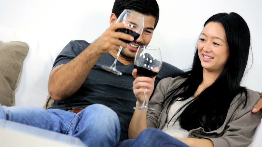 Casually dressed relaxed young Asian Chinese couple enjoying time together  talking drinking glass wine home sofa