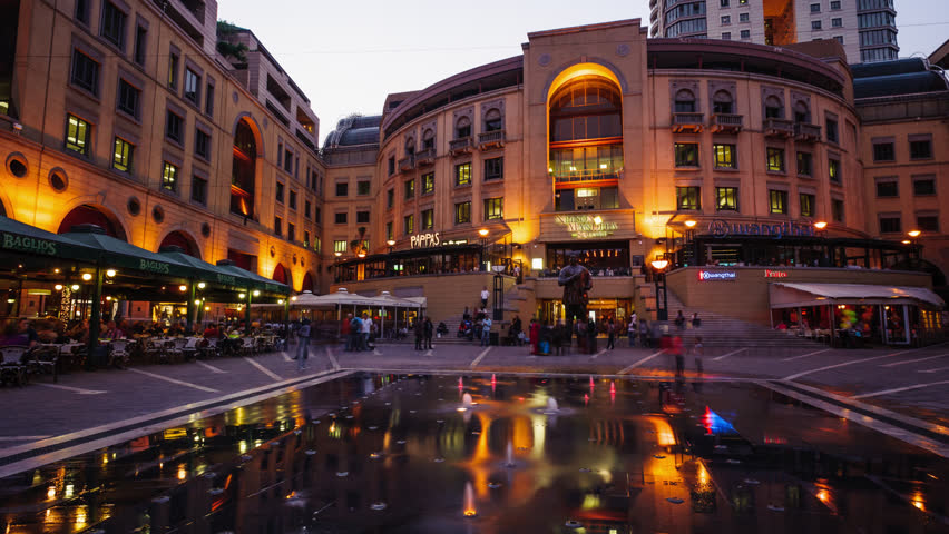 Sandton, Johannesburg, Gauteng, South Africa - 22/09/2012  Nightfall at the Nelson Mandela Square in Sandton, Johannesburg overlooking statue of Nelson Mandela next to the restaurants and fountain.