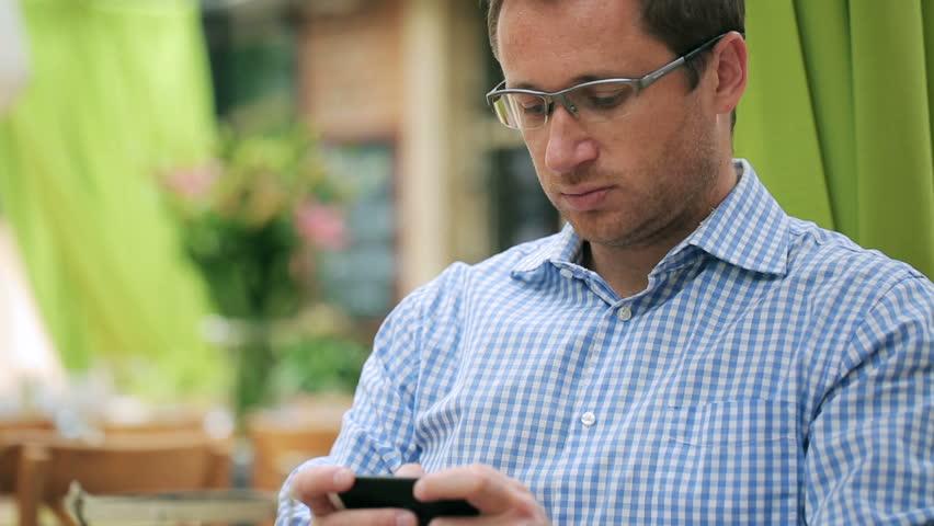 Man using cellphone in restaurant, steadycam shot  | Shutterstock HD Video #6702407