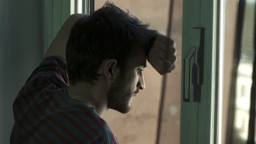 Portrait of handsome young sad man in front of a window, 4k | Shutterstock HD Video #6704321