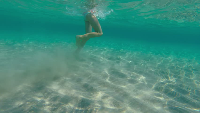 Little girl plays and runs around in shallow water in sea. Underwater shot. #6771457