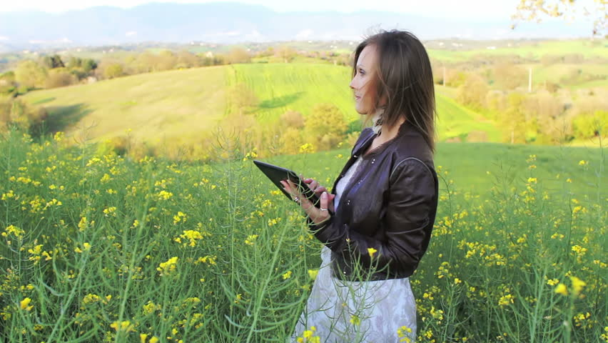 girl with long blond hair and digital tablet PC in yellow rape field