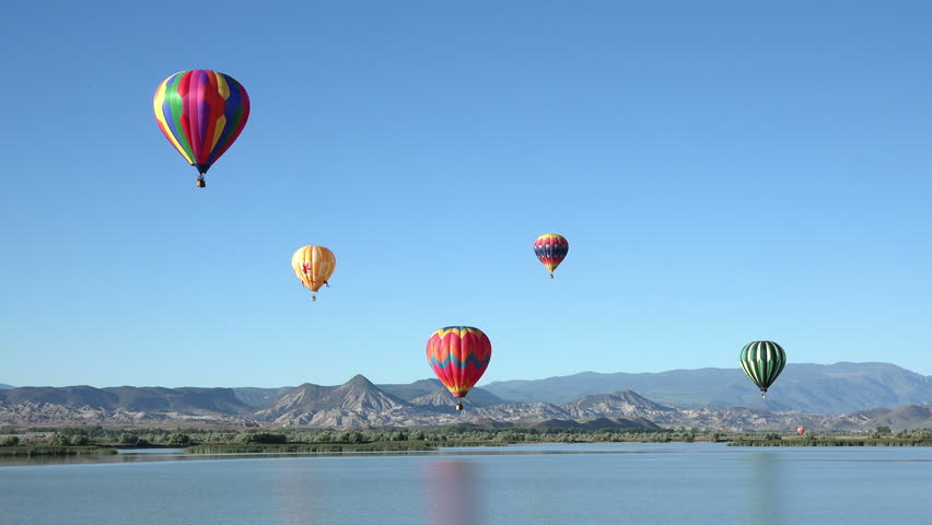 SALINA, UTAH - JUN 2014: Colorful hot air balloon flight over rural lake. Pilot fly slow moving aircraft. Early morning community festival has annual Balloon Fest and competition. Mountain valley. | Shutterstock HD Video #6794887