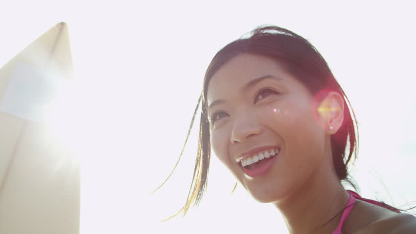 Close up head shot young Asian Chinese female surfer living healthy outdoor lifestyle holding her board waiting for waves sun lens flare shot on RED EPIC