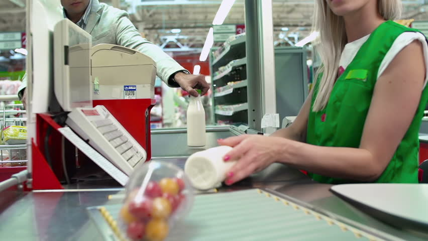 Close up of check till and products on conveyor belt, people are unrecognizable
