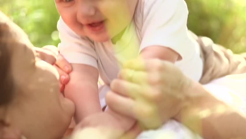 Mother and Baby having fun Outdoors.Together in Green Summer Park. Mom and Child. Happy Family Smiling. Beautiful family in spring park enjoying nature. Slow motion 1920x1080 | Shutterstock HD Video #6853525