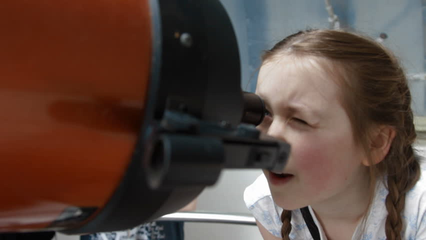 A little girl using a large telescope
