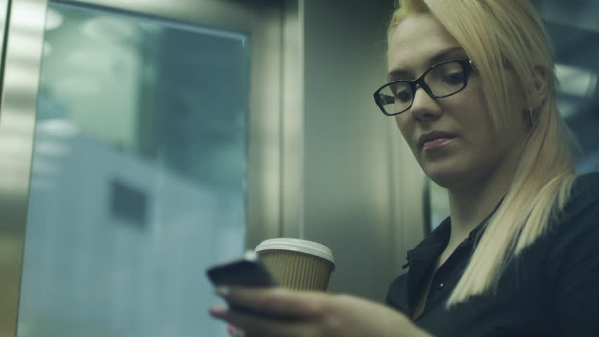 Woman Drinking Coffee and Using Mobile Phone in Elevator. Shot on RED Digital Camera in 4K, so you can easily crop, rotate and zoom. ProResHQ codec - Great for editing, color correction and grading. | Shutterstock HD Video #6857227