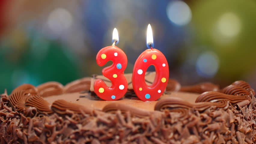 Candles On A Cake Are Blown Out For 30th Birthday