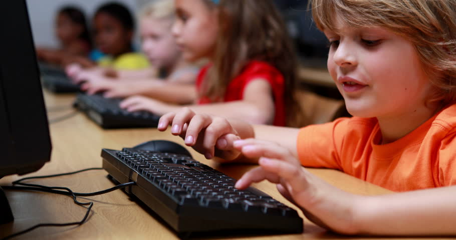 Little boy smiling at camera during computer class in elementary school | Shutterstock HD Video #6866461