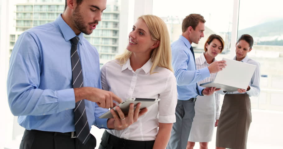 Business team using tablet and smiling at camera together in the office | Shutterstock HD Video #6868342
