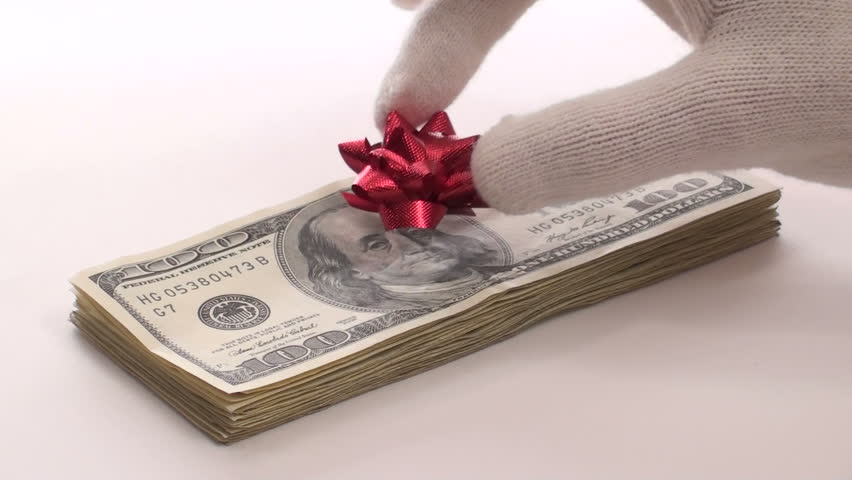 Generous Santa places festive bow on stack of hundred dollar bills isolated on white
