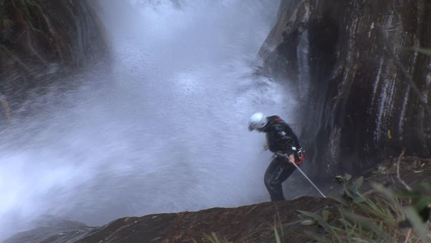 A canyoneer canyoning under strong waterfall pressure