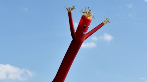 A shot of a red wacky waving inflatable arm flailing tube man.
