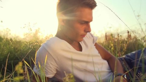 Handsome teenage guy lying on the field. Young man enjoying nature outdoors. Looking an camera and smiling. Slow motion 240 fps full hd video footage 1080p. High speed camera shot