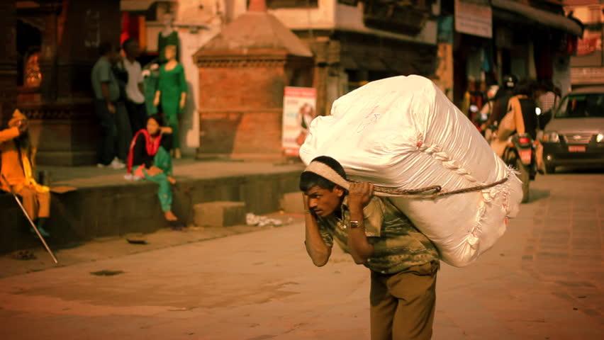 KATHMANDU, NEPAL, CIRCA MAY 2014 – Man transports large load of freight circa May 2014 in Kathmandu, Nepal. Kathmandu is the capital and largest urban agglomerate of Nepal.